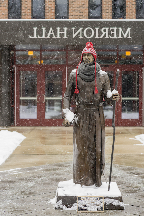 Saint Ignatius statue wears a winter hat while it snows
